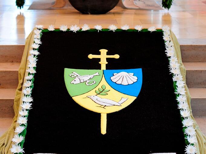 Blumenteppich mit Bischofs-Wappen und Wahlspruch. (Foto: Nicolas Schnall)
