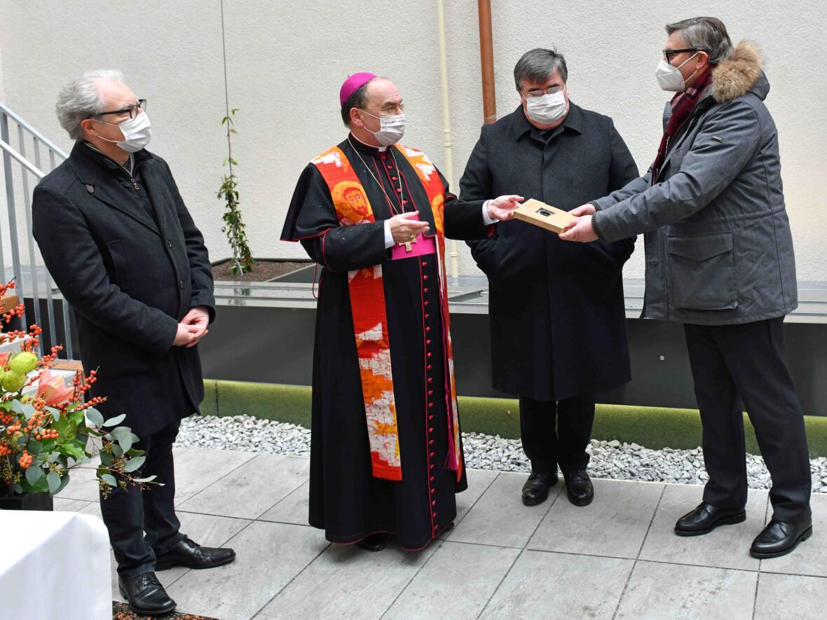Bischof Bertram reicht die Chipkarte an Finanzdirektor Quella weiter.
