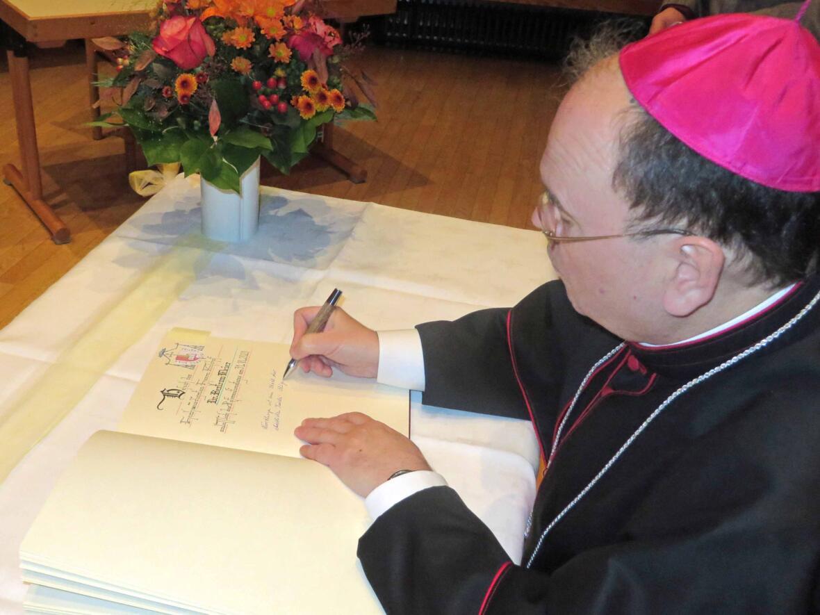 Bischof Bertram Meier trägt sich ins Goldene Buch der Stadt Nördlingen ein