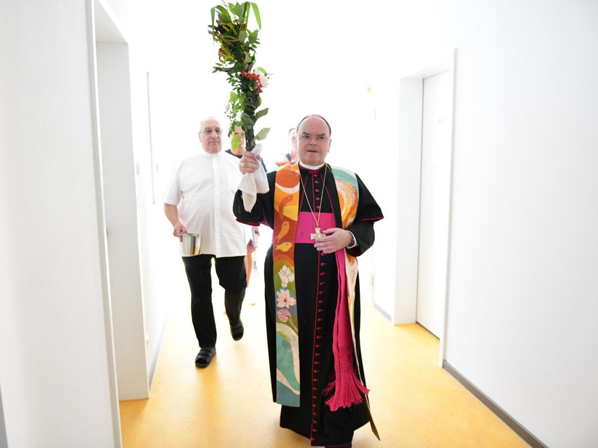 Der Bischof weiht das neue Wohnheim ein. Als Weihwasserpinsel verwendete er dabei einen Büschel mit Blumen und Gräsern aus dem Garten des Abbé-Pierre-Zentrums.