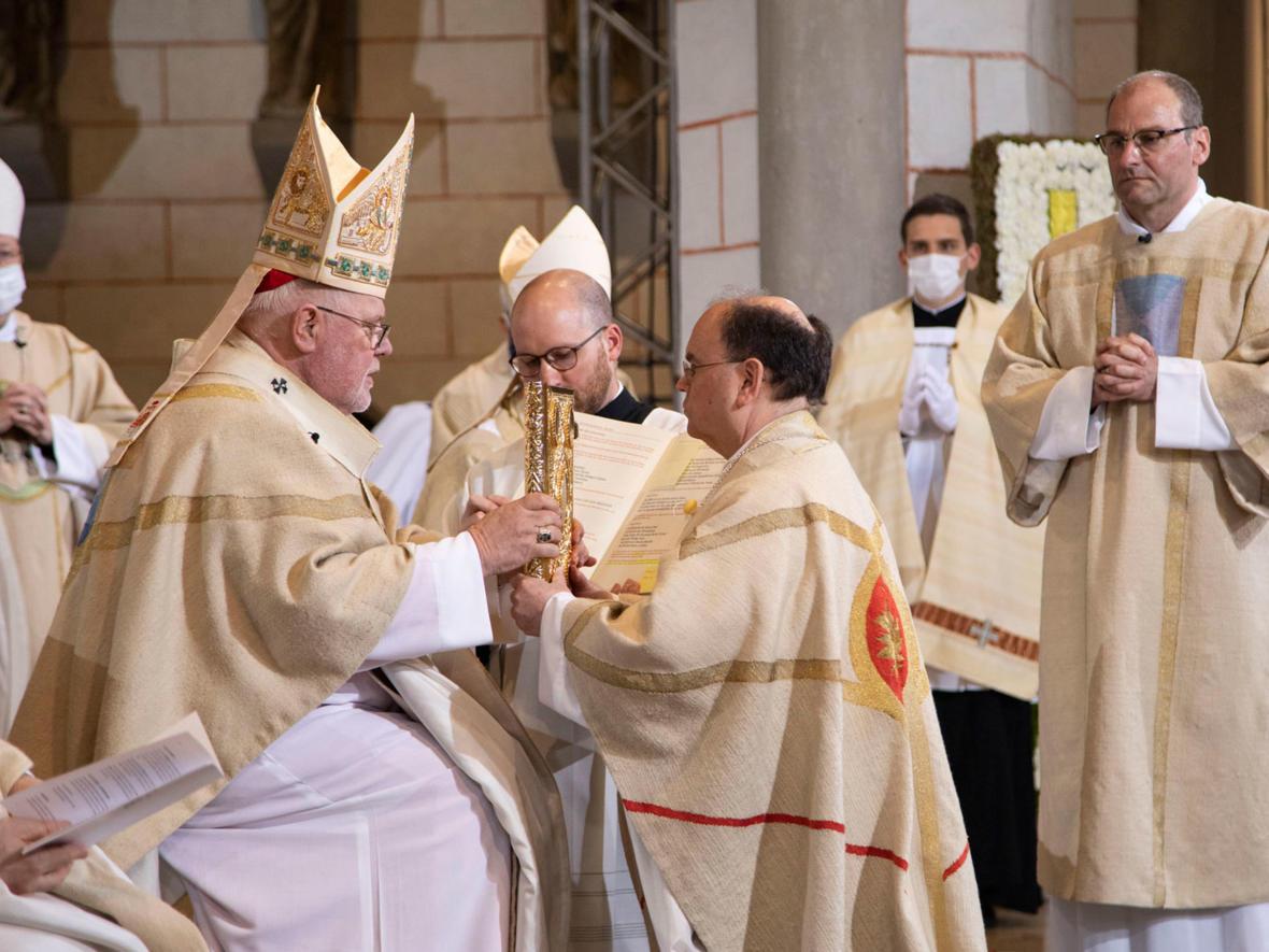Kardinal Marx überreicht Bischof Bertram das Evangelium (Foto: Anika Taiber-Groh / pba)