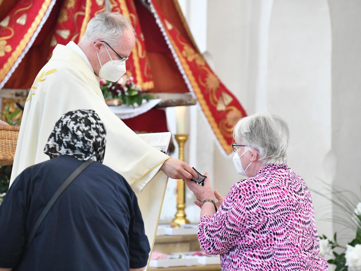 Pfarrer Sebastian Nößner überreicht den Neumitgliedern ihr Skapulier