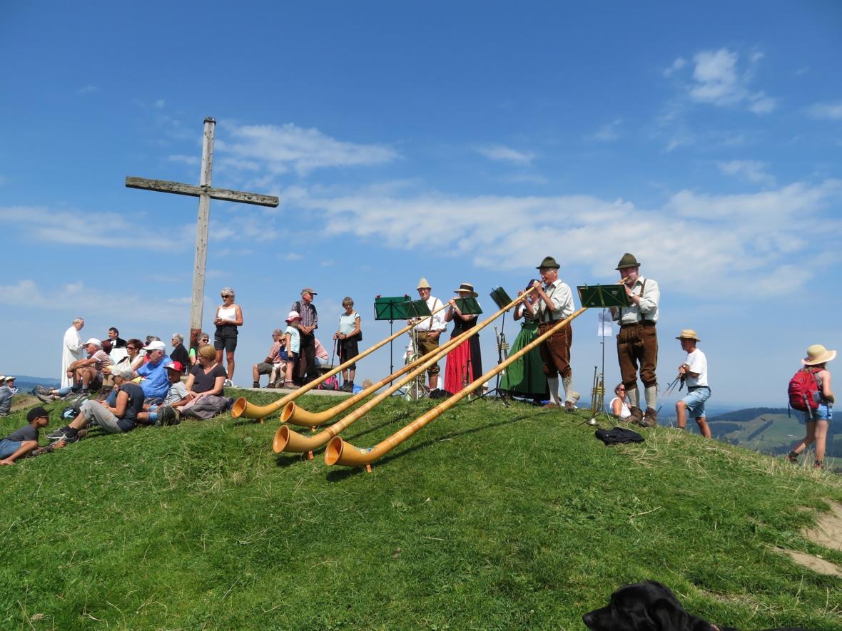 Pfarrer Frank Wagner und Pastoralreferent Josef Hofmann feiern von Anfang Juni bis Ende September jeden Freitag um 11.30 Uhr einen ökum. Berggottesdienst am Gipfelkreuz des Hündle. Die musikalische Gestaltung übernahm am 20.7.18 die Allgäuer Alphorn- und Bläsergruppe aus Leutkirch.