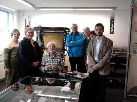 Herr Wilhelm an der Linotype mit den Archivmitarbeiterinnen und -mitarbeitern
