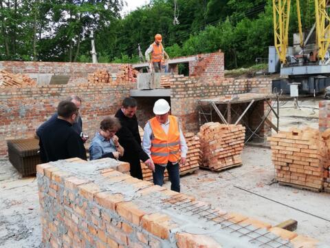 Der Bau des Exerzitienhauses mit Landwirtschaftsschule in Zarvanytsia geht voran. Andrea Decke (zweite von links) und Anton Stegmair (nicht im Bild) erhielten eine Führung von Ökonom Mitrat Volodymyr Firman (links) durch die Baustelle.