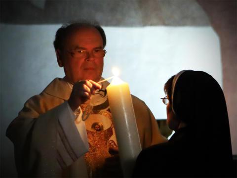 Christus ist auferstanden! Bischof Bertram entzündet die Osterkerze während der Feier der hl. Osternacht in der Kapelle des Bischofshauses (Foto: Annette Zoepf / pba)