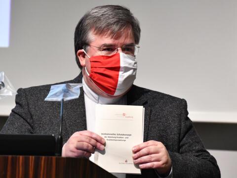 Generalvikar Harald Heinrich mit dem Schutzkonzept der Kranken- und Krankenhausseelsorge (Foto: Julian Schmidt / pba)