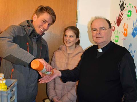 Der künftige Bischof von Augsburg, Prälat Dr. Bertram Meier, lässt sich von Oberministrant Michael Hock die Farbe für einen Handabdruck an der Wand des Ministranten-Treffs auftragen. (Foto: Verspohl-Nitsche / pdke)