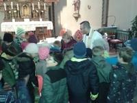 Foto: Stadtpfarrer De Blasi zeigt den Erstkommunionkindern verschiedenste Bibelausgaben.