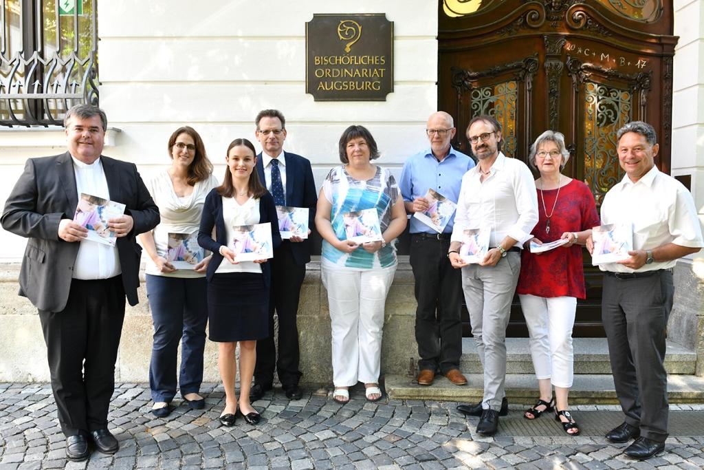Noch druckfrisch: Die ersten Exemplare der Broschüre hat Generalvikar Heinrich soeben der Projektgruppe sowie der Mitarbeitervertretung überreicht. (Foto: Daniel Jäckel / pba)