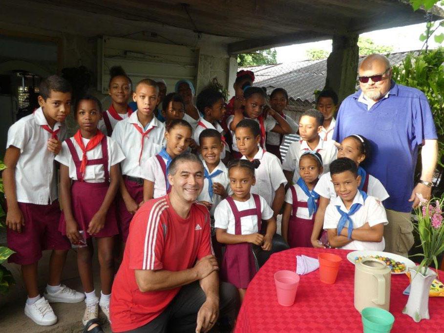 Der kubanische Missionspfarrer Otto Anderco und Wolfgang Friedel von der Caritas Augsburg mit Schulkindern auf Kuba (Foto: Caritas Augsburg / Wolfgang Friedel)