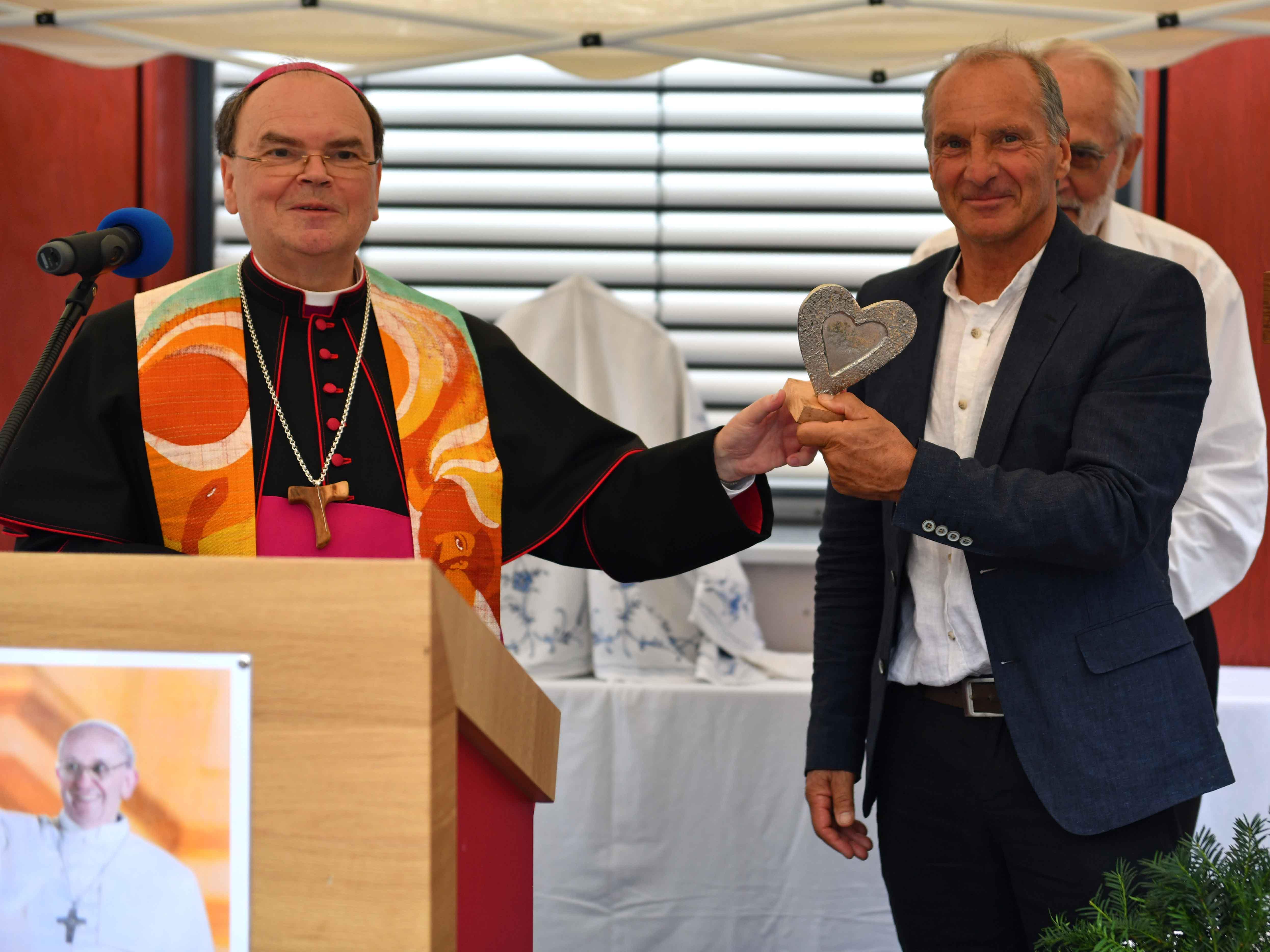 Bischof Dr. Bertram Meier überreicht Caritas-Geschäftsführer Dr. Walter Semsch ein Herz als Symbol für die Arbeit der Caritas. (Fotos: Julian Schmidt / pba)