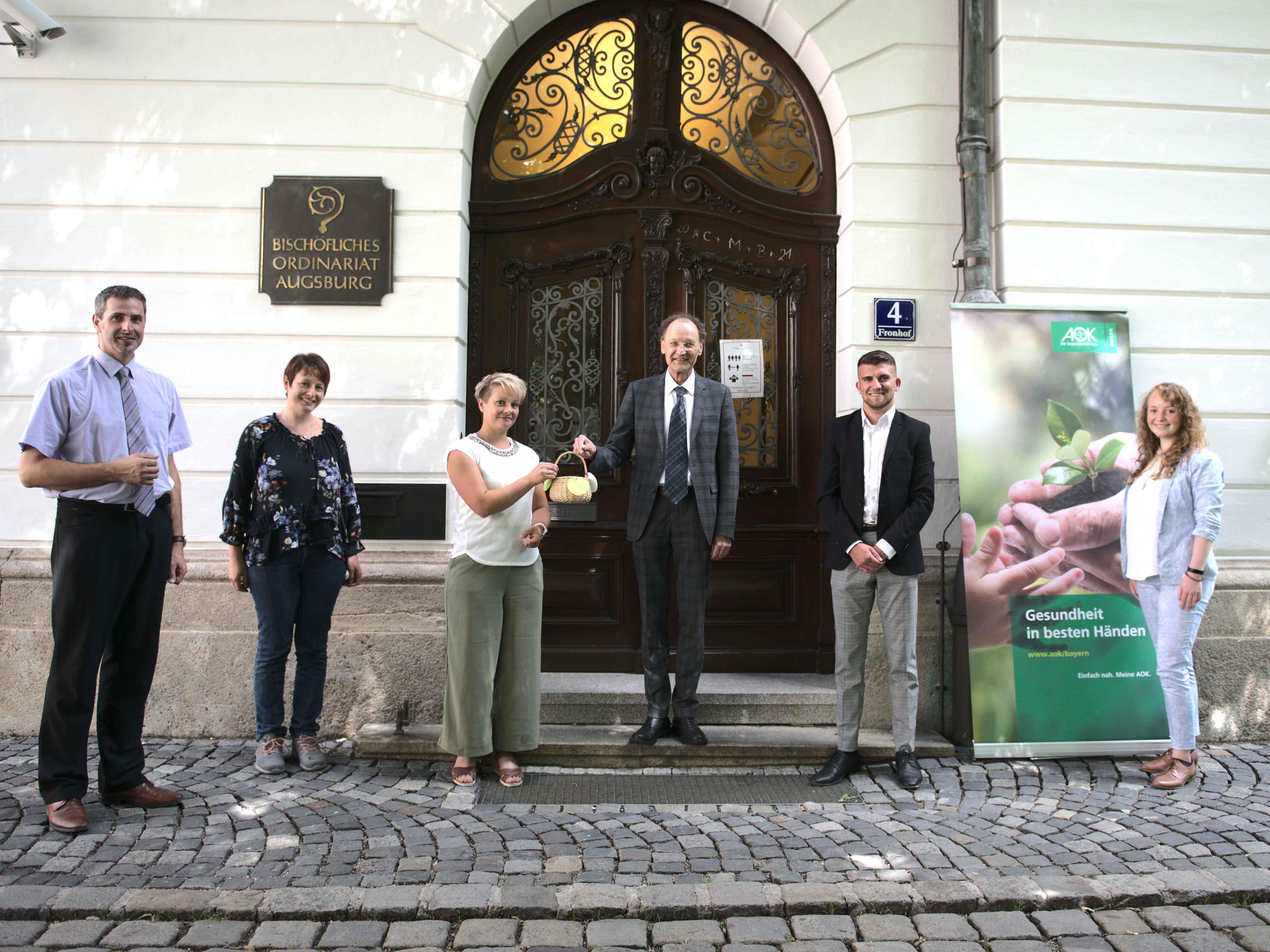 Generalvikar Dr. Wolfgang Hacker hat per Losziehung die Gewinner des Gesundheitstags ermittelt. Neben dem Projektteam waren auch Mitarbeiter der AOK Bayern dabei (Maria Steber / pba).