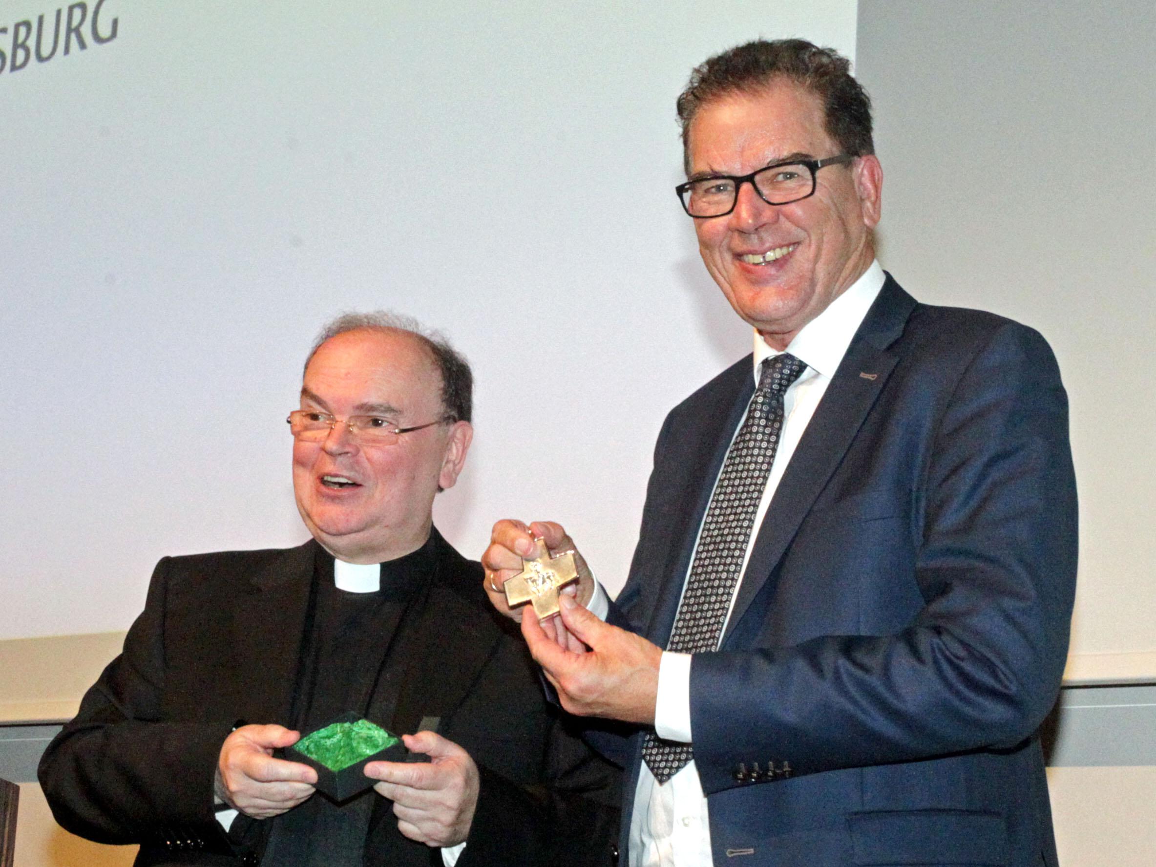 Diözesanadministrator Bertram Meier überreicht Minister Müller das Ulrichskreuz.