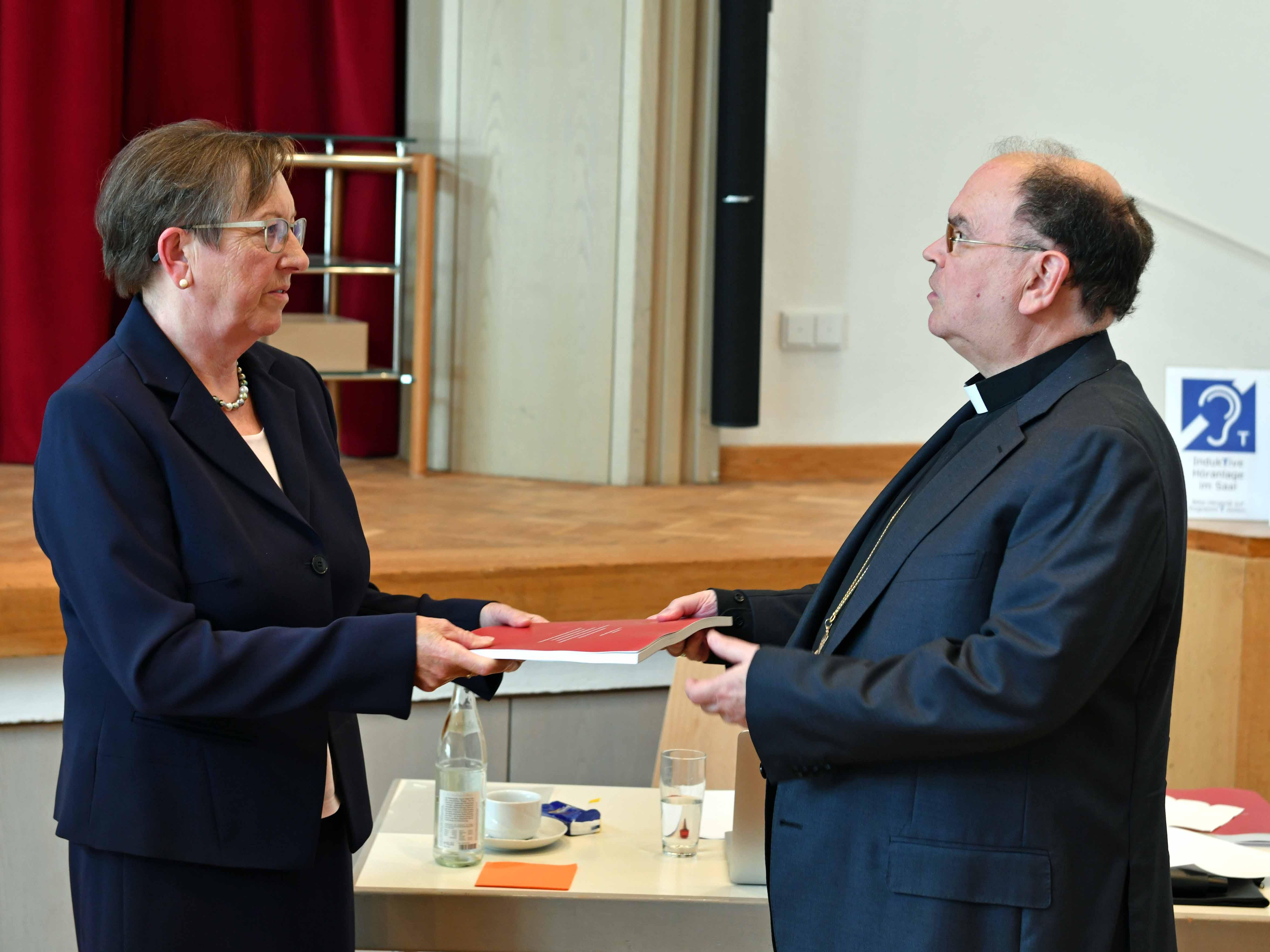 Die Leiterin der Projektgruppe Reitenbuch Elisabeth Mette überreicht Bischof Dr. Bertram Meier den Abschlussbericht. (Foto Nicolas Schnall / pba)