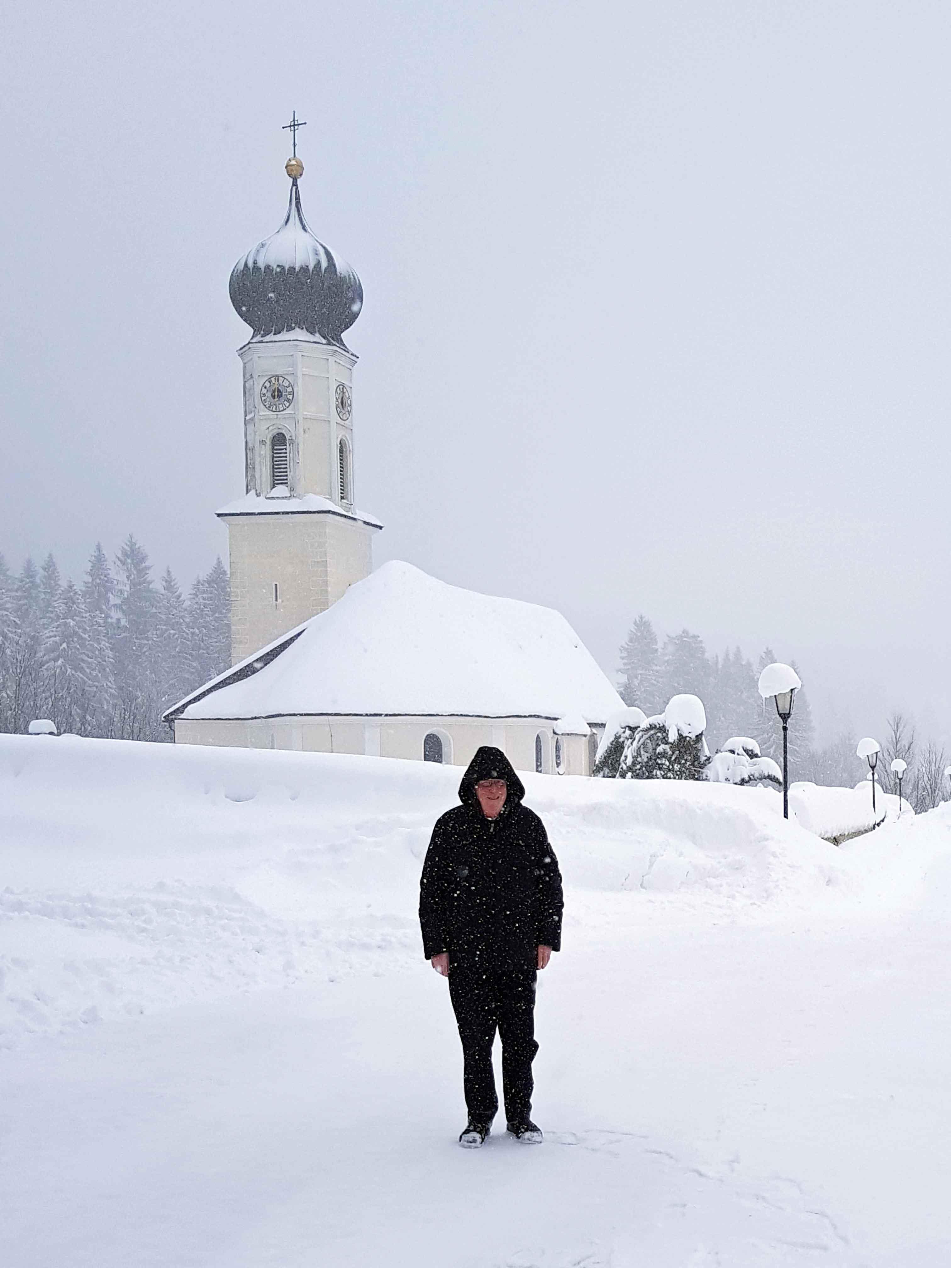 Nimmt die Situation mit Humor und einer gesunden Portion Gelassenheit: Pfarrer Willi Milz vor seiner von Schneemassen umgebenen Pfarrkirche St. Nikolaus. (Foto: privat)