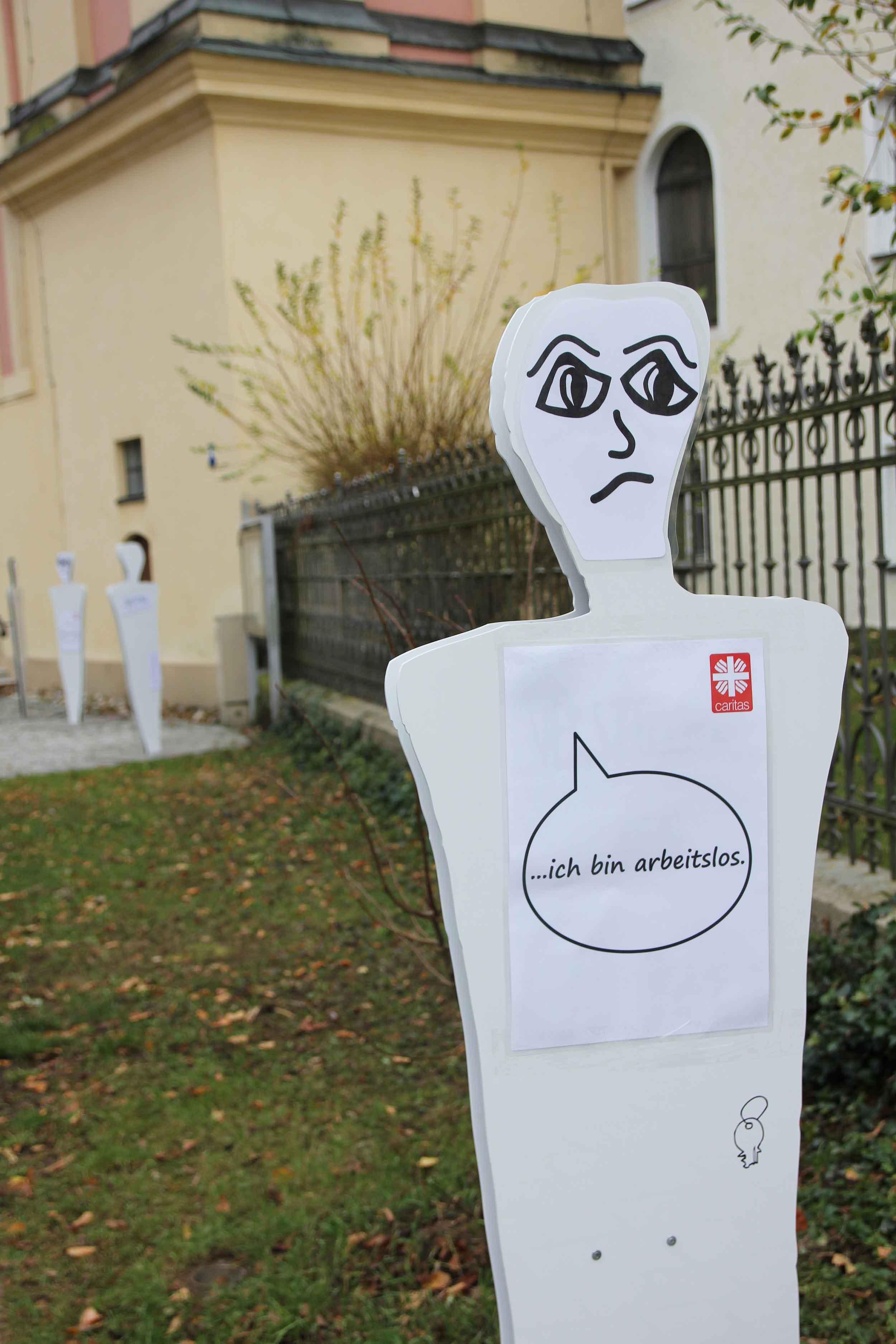 Lebensgroße Figuren auf dem Vorplatz der Heilig Geist Kirche in Neuburg machen auf Armutssituationen aufmerksam (Foto: Bernhard Gattner / Caritas).