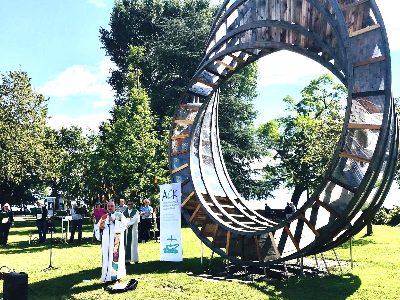 """Bischof Bertram vor dem """"Ring of Peace"""" auf dem Gelände der Gartenschau Lindau (Foto: Fachbereich Kirche und Umwelt im Bistum Augsburg)."""