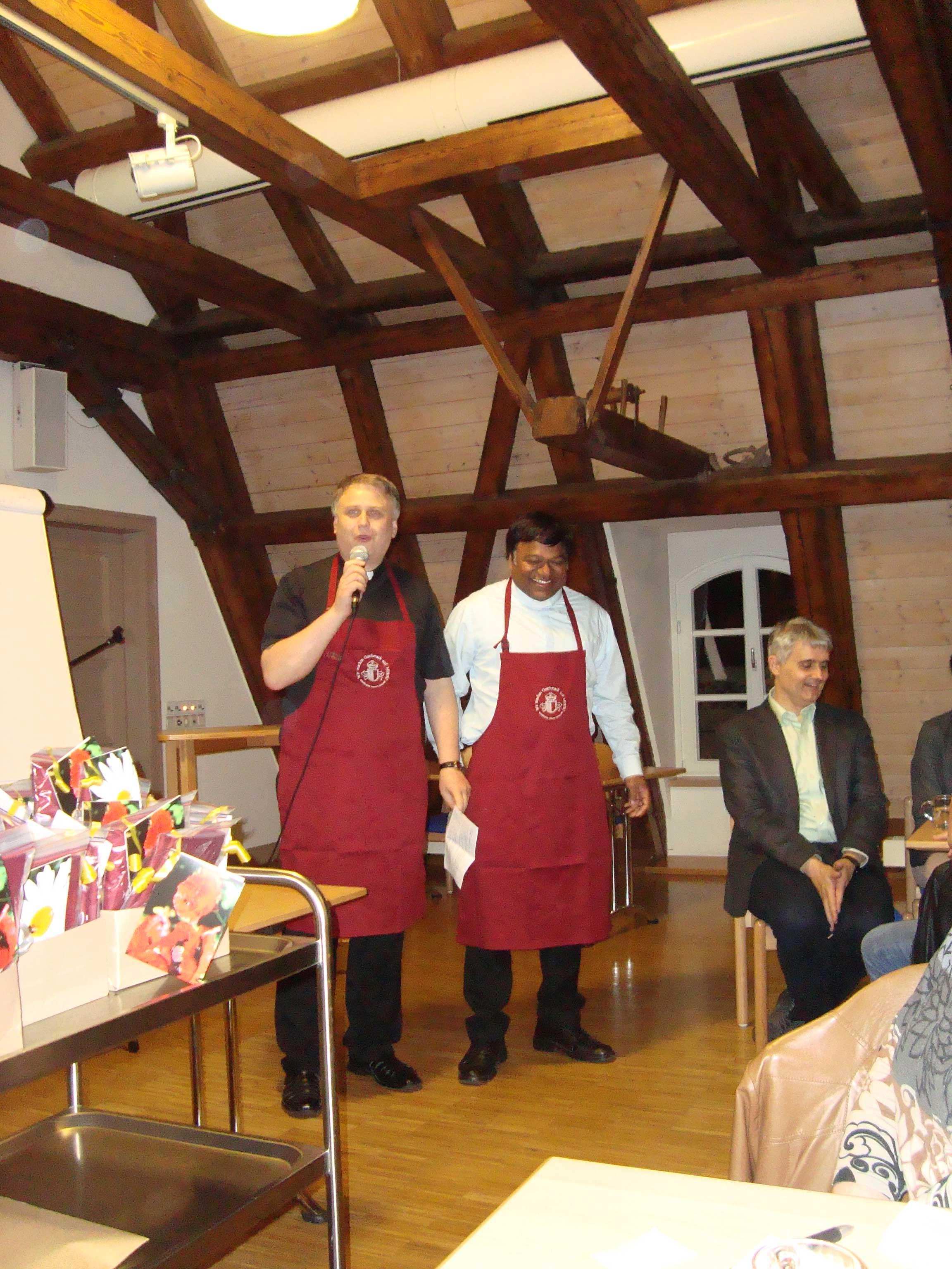 """BU """"Dekan und Prodekan mit Schürzen"""": Dekan Andreas Straub und Prodekan Eli Fernandes (von links) bedankten sich mit einem heiteren Beitrag und Grillschürzen bei den Dekanatsräten der vergangenen Wahlperiode."""