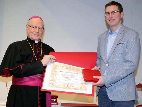 """Pavel Jerabek erhält von Bischof Konrad Zdarsa das päpstliche Ehrenkreuz """"Pro Ecclesia et Pontifice"""" (Foto: Annette Zoepf / pba)"""